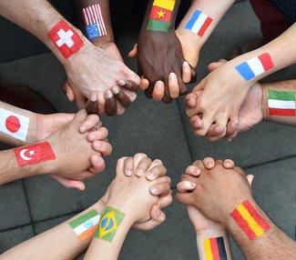 Photo of a circle of joined hands; different flags painted on each wrist